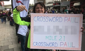 Volunteer Kay Reynolds, standing at mile 21, holds up a word for Paul to come up with a suitable clue.