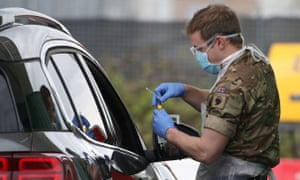 A soldier tests a key worker at a drive-through centre at Glasgow airport