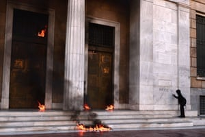 A youth writes 'burn it' on the facade of the headquarters of the Bank of Greece as molotov cocktails thrown by demonstrators burn during a demonstration in Athens