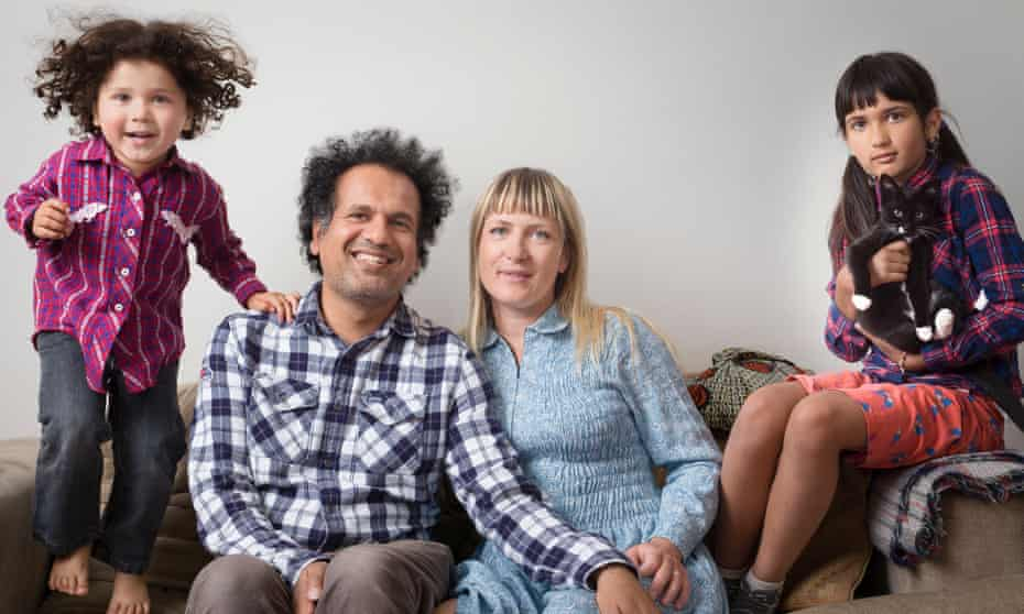 Sarfraz Manzoor and his wife Bridget, on the sofa at home with their children, Ezra, 3, jumping up and down, and Laila, eight, holding the family cat.