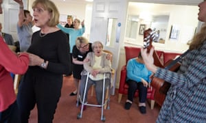 Care workers and elderly residents at a music therapy group session  in Oxfordshire