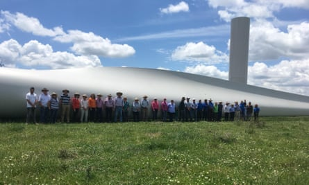 Local landowners dwarfed by a Sapphire Wind Farm turbine blade in the New England region of northern NSW.