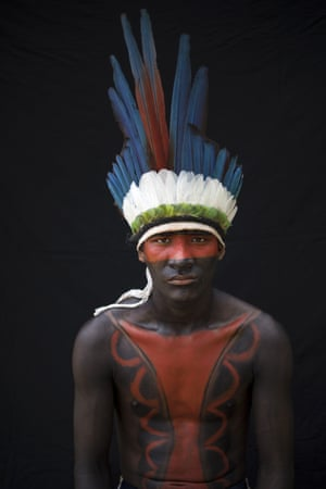 Gelson Tembe, 21, poses for a portrait during a meeting of the Tembe tribes in the Tekohaw village, in the Alto Rio Guama Indigenous Reserve, Para state, Brazil. Tembe warriors wear colorful headdresses of macaw and other feathers, and wield bows and arrows for hunting and to protect their homeland, which is constantly under threat in the globally vital Amazon region