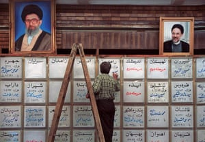 Under portraits of Iranian President Mohammad Khatami, right, and Iran's supreme leader Ali Khamenei, a caligrapher of the Interior Ministry writes results of the Parliamentary elections on a board in Tehran on 21 February 2000.