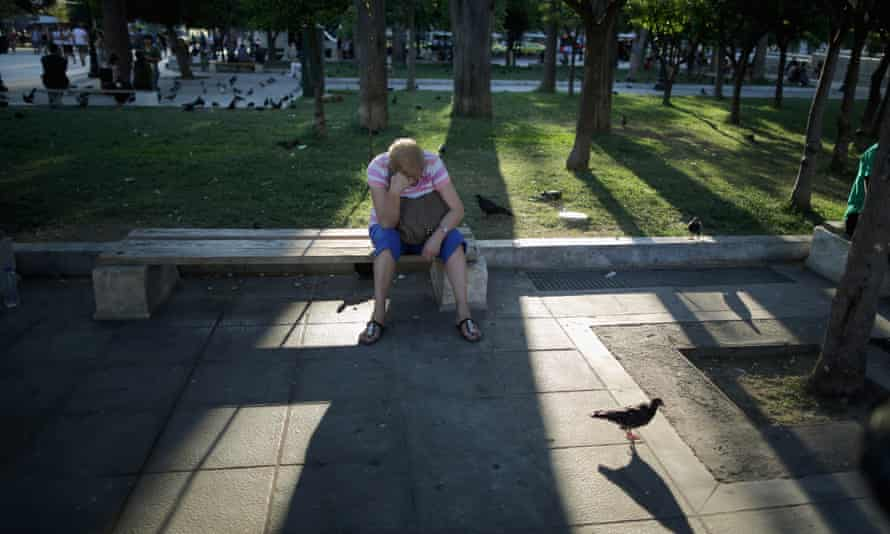 A woman sitting, dead turned down, on a bench