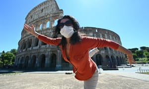 A woman holds a yoga posture as she exercises by the Colosseum in Rome.