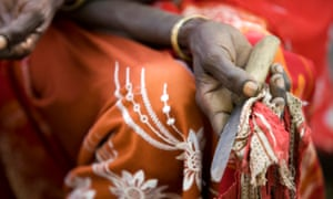 A former cutter holding the tool she used to carry out female genital mutilation, which is illegal in Burkina Faso.