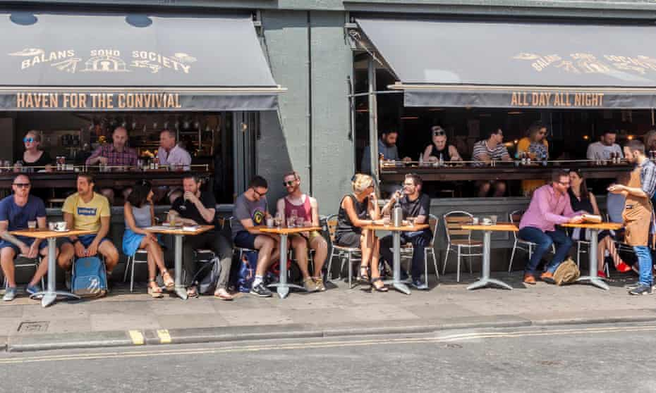 Customers relaxing, eating and drinking inside and outside a bar and brasserie in London