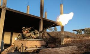 A fighter from the former al-Qaida affiliate Hayat Tahrir al-Sham fires an anti-aircraft gun in southern Idlib province