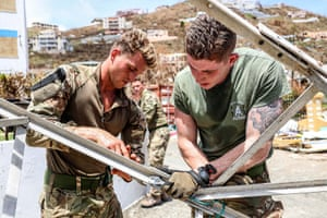 Royal Marines move a collapsed radio mast that has been blocking crucial access within the police station on Tortola.