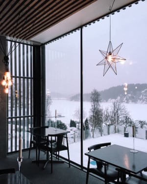 View looking out from the restaurant of the Vann hotel and spa onto snow covered trees and hills in the Gullmar fjord nature reserve, Sweden.