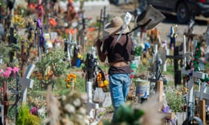 A gravedigger works at a cemetery in Valle de Chalco in Mexico where the pandemic has now killed more than 100,000 people.