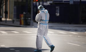 A healthcare worker walks in protective gear in Brooklyn on Thursday.