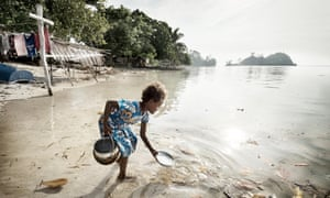 A girl washes dishes in the sea