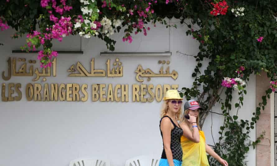 Tourists pass the Orangers Beach hotel in the Tunisian coastal town of Hammamet