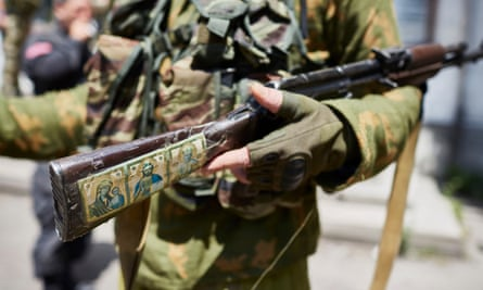Religious images on the rifle of one of the Ghost Brigade fighters.