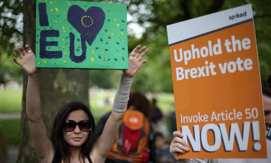 A woman holds a pro-EU placard next to a Brexit supporter