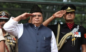 The Jammu and Kashmir governor, Satya Pal Malik, left, salutes after hoisting the Indian national flag during the celebrations for India's independence day.