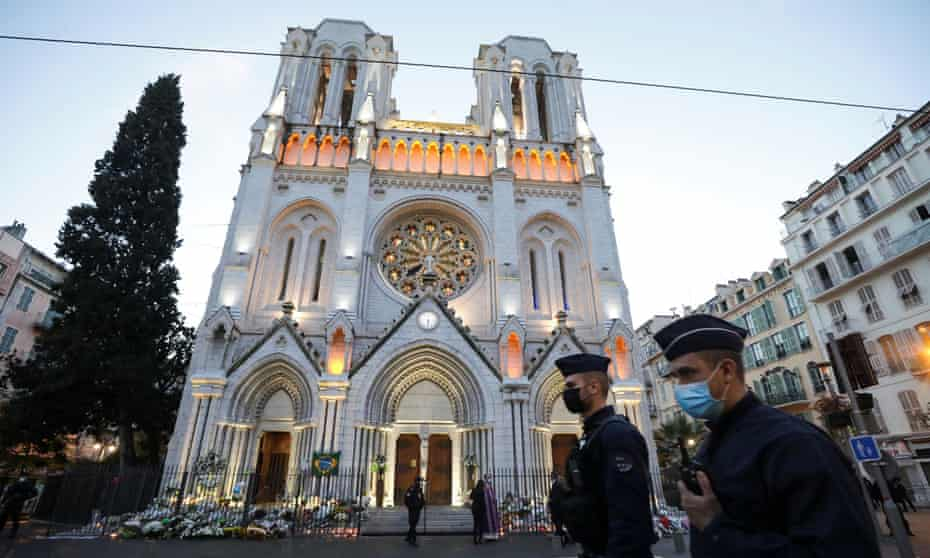Police officers walk in front of the Notre Dame church before a mass to pay tribute to the victims of the knife attack in Nice.