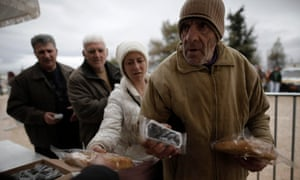 Greeks line-up to receive free olives and bread distributed for free Athens council on the start of Lent in Greece.