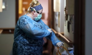 A nurse prepares for work at a nursing home in England.