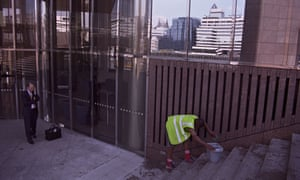 A cleaner in front of a building in the City of London