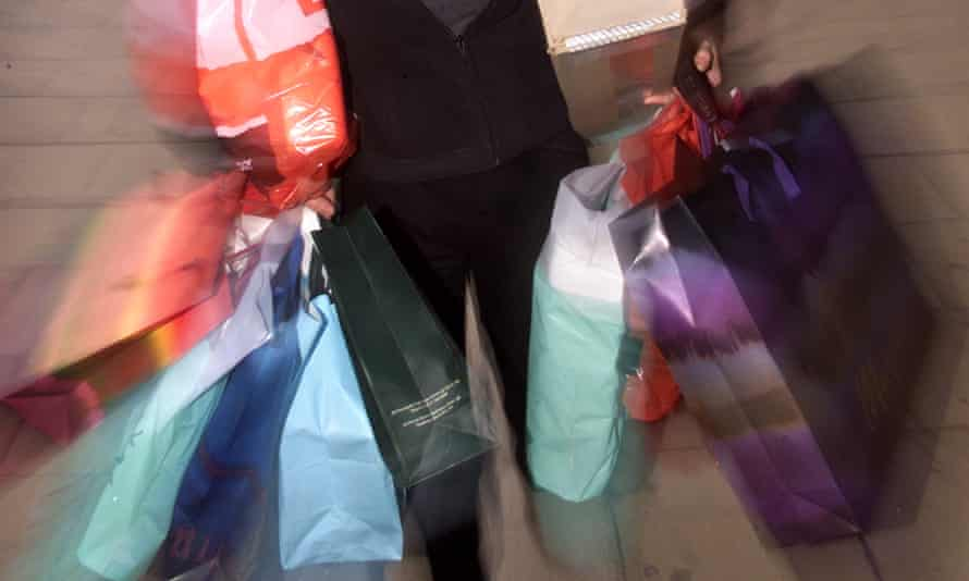 A soft-focus close-up of a woman carrying colourful shopping bags