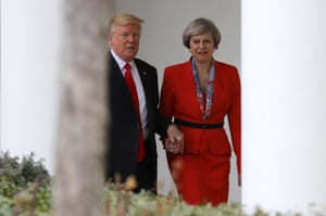 Theresa May holds hands with Donald Trump