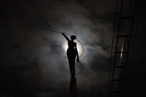 A sculpture is silhouetted against a full moon in Brussels
