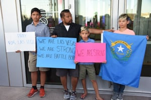 People hold signs and the Nevada state flag during a vigil at Las Vegas City Hall