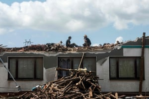 South Moravia, Czech Republic: Two men clean sit on a damaged roof after a tornado tore through several Czech villages and towns.