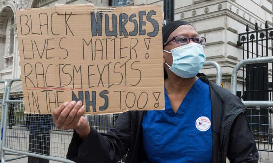 An NHS nurse holds a sign saying 'Black nurses'lives matter! Racism exists in the NHS too!'