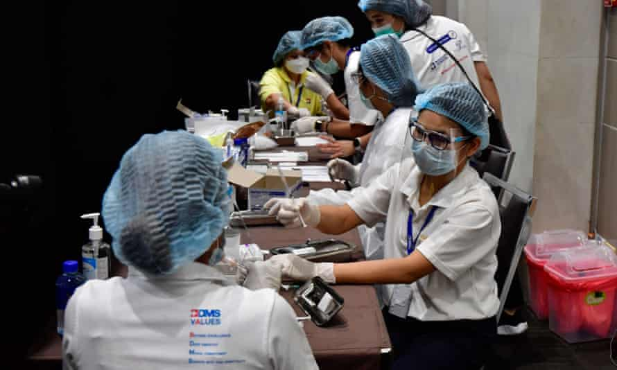 Health workers prepare to administer Covid jabs at a vaccination site in the Siam Paragon shopping mall in Bangkok