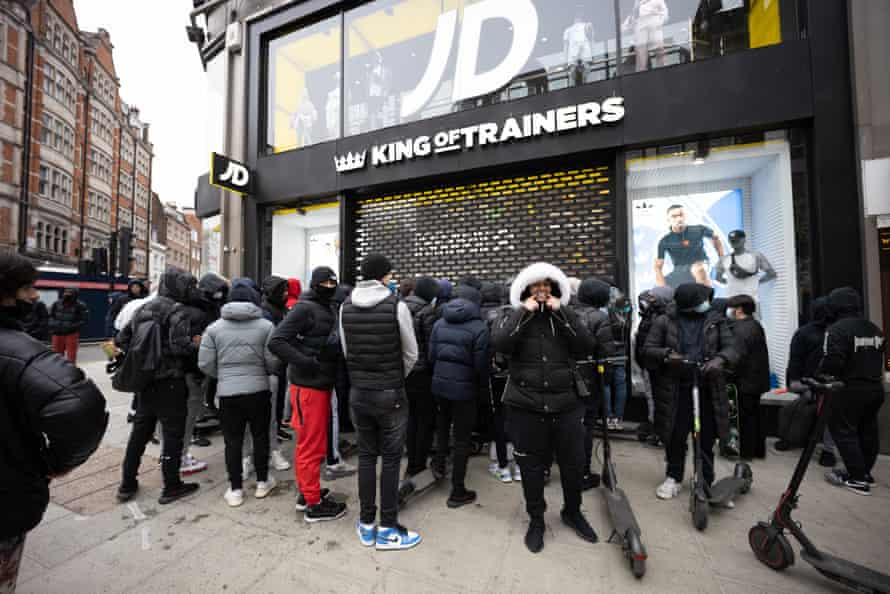 People waiting to buy trainers queue outside JD Sports in Oxford Street in London.
