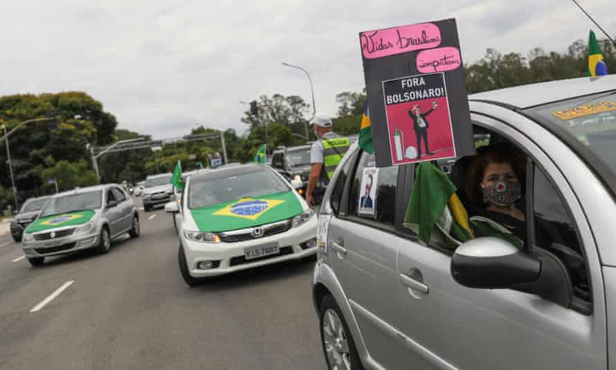 A woman holds up a sign reading 'Brazilian lives matter. Out Bolsonaro!' during a motorcade in São Paulo.