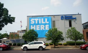 A banner stating 'STILL HERE' hangs on the side of the Planned Parenthood building after a judge granted a temporary restraining order on the closing of Missouri's sole remaining clinic in St Louis.
