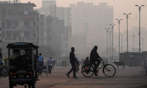 People make their way along a street amid smoggy conditions in New Delhi on 15 November 2020.