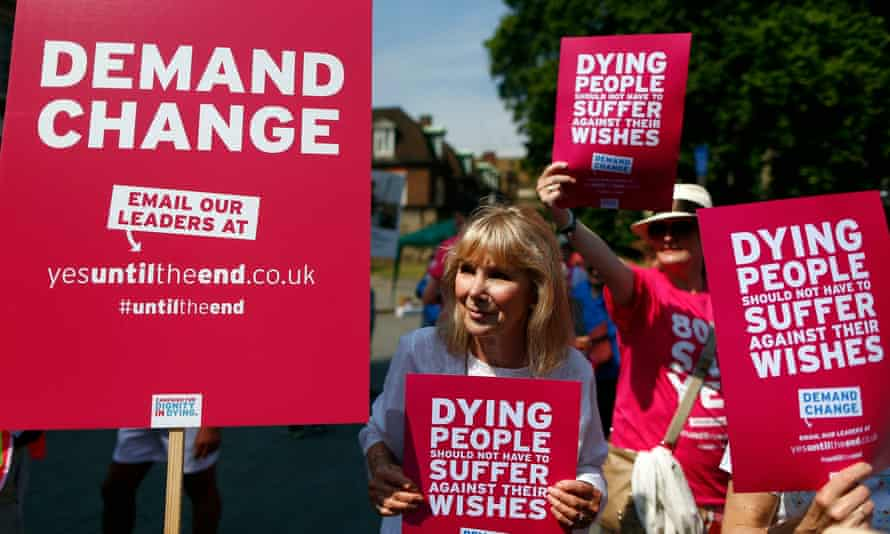 Supporters of a bill legalising assisted dying hold placards outside parliament in Westminster, central London.
