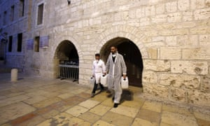 Employees of a private company walk out of the Church of the Nativity in the West Bank city of Bethlehem, after spraying sanitisers as a preventive measure against the coronavirus, on March 5, 2020.