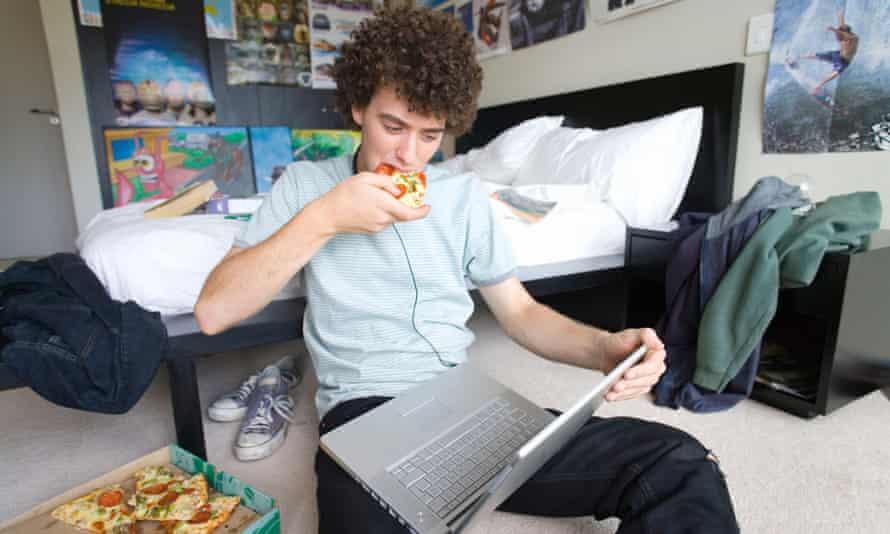 Băiat adolescent așezat pe podeaua dormitorului cu laptop și pizza