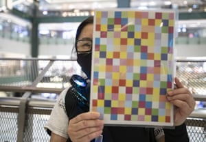 A woman holds up a self-printed mini 'Lennon Wall' during a protest in a mall in Hong Kong in August.