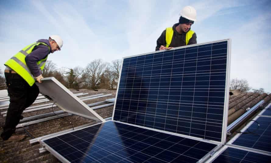Fitters install solar panels on a barn roof at Grange farm, near Balcombe in west Sussex, England.