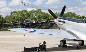 Pilot shelters from sun under wings of Spitfire at  international air event at RAF Fairford