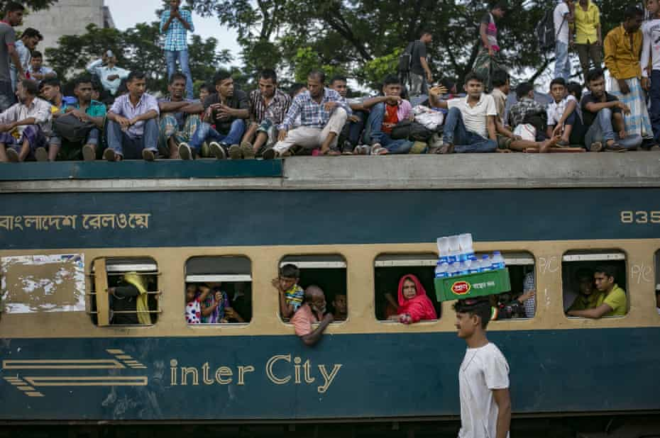 Bangladeshis aboard a packed train travel home to their villages from Dhaka
