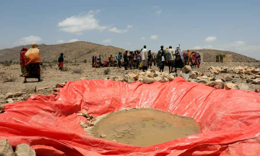 Displaced people gather at an artificial water pan near Habaas, a town in the disputed Awdal region