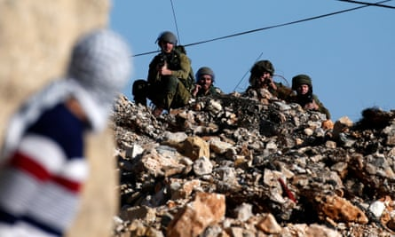 A Palestinian protestor looks towards Israeli security forces