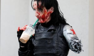 An attendee in costume as the Winter Soldier grabs a drink