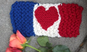 A knitted French flag with a heart design lies beside a rose on the pavement outside the French consulate in Boston, USA