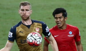 Per Mertesacker of Arsenal is checked by Khairul Amri of Singapore during the Barclays Asia Trophy match between Arsenal and Singapore at National Stadium on July 15, 2015 in Singapore. (Photo by Stanley Chou/Getty Images)