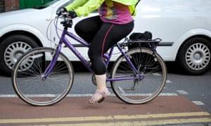 A person cycling alongside a car in Bristol